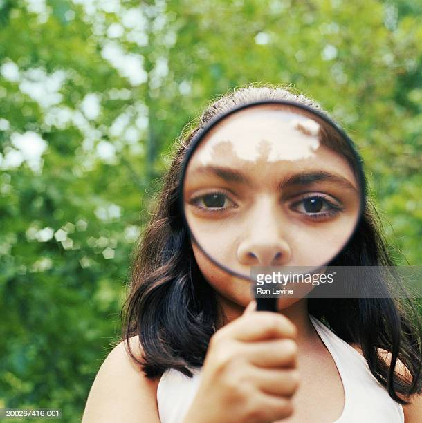 Girl (10-12) holding magnifying glass to her face