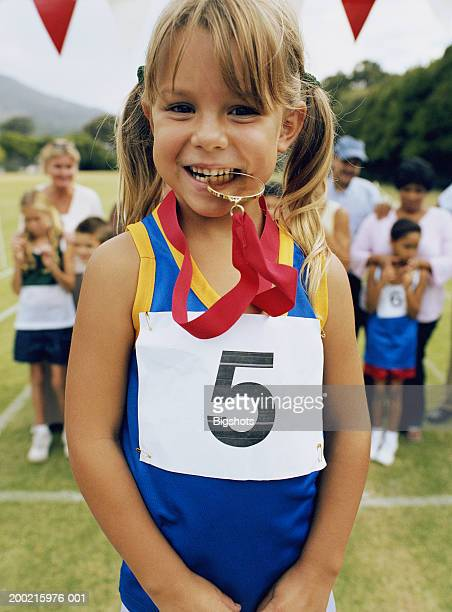 Girl (5-7) holding medal between teeth, smiling, portrait