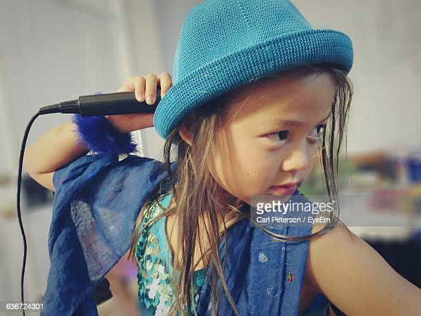 Girl Holding Microphone While Looking Away At Home