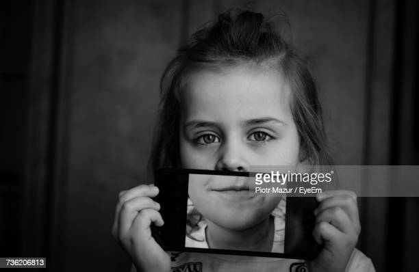 Girl Holding Mobile Phone In Front Of Face