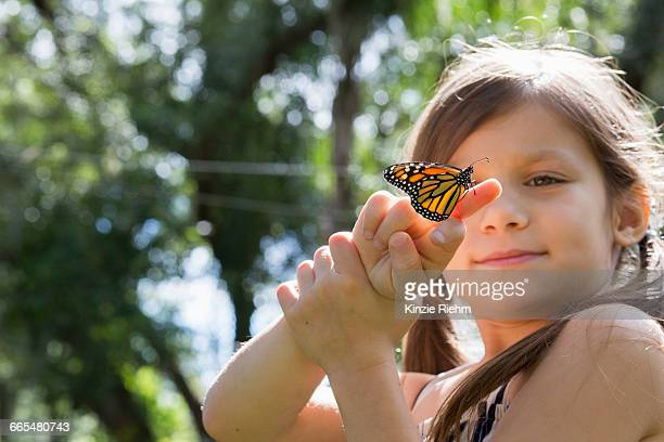 girl holding monarch butterfly on finger - mariposa monarca fotografías e imágenes de stock