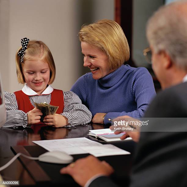girl holding money at a bank - family dollar stock pictures, royalty-free photos & images