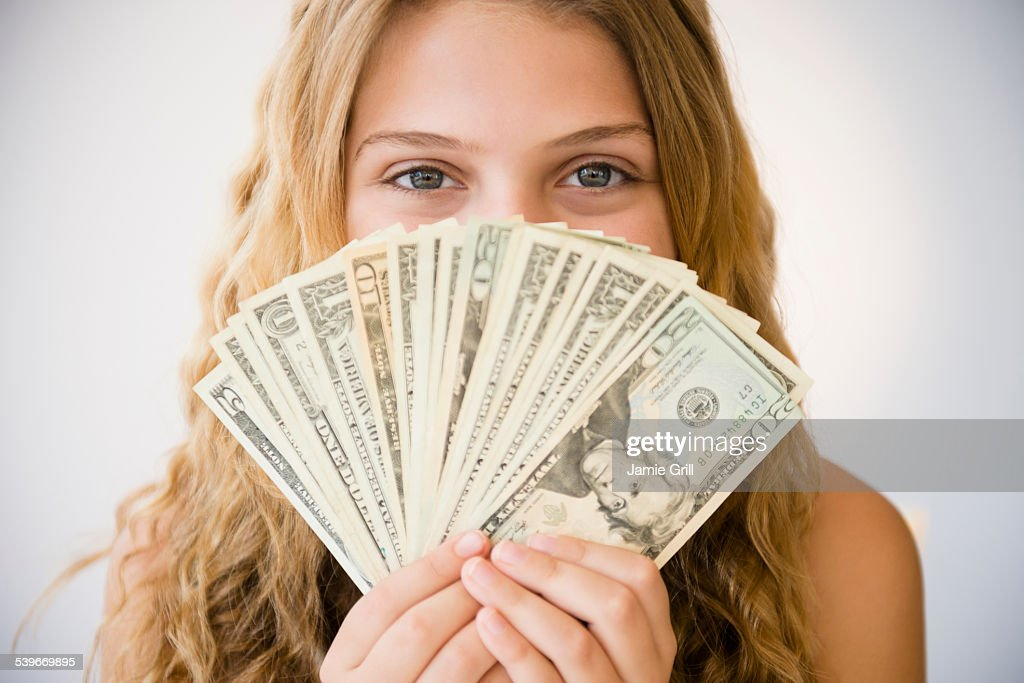 Girl (12-13) holding money fan against her face : Stock Photo