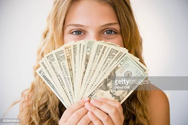 Girl (12-13) holding money fan against her face