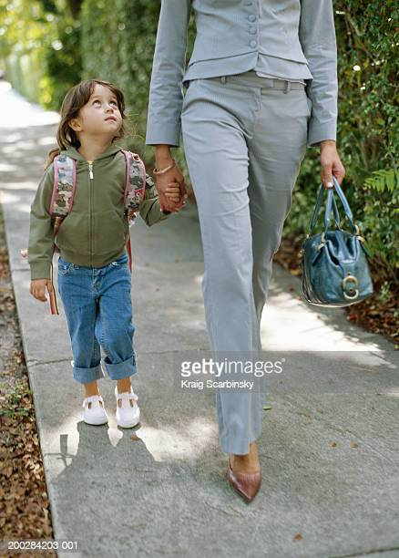 Girl (4-6 years) holding mother's hand, walking along pavement