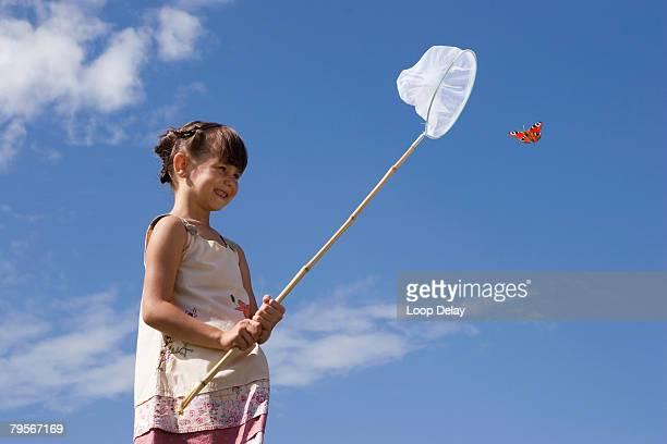 girl (7-9) holding net, trying to catch butterfly - fangen stock-fotos und bilder