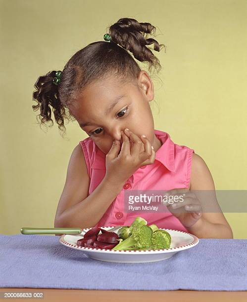 Girl (4-6) holding nose while looking at plate of vegetables