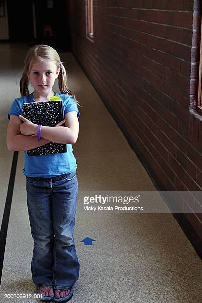 girl (7-9) holding notebook in school corridor, portrait - girl wear jeans and flip flops stock photos and pictures