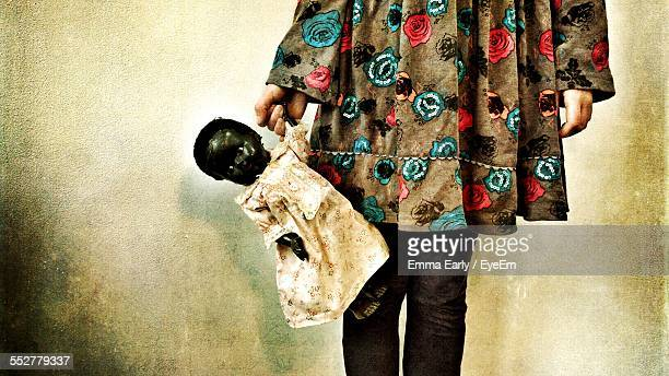 Girl Holding Old Doll By Wall At Home