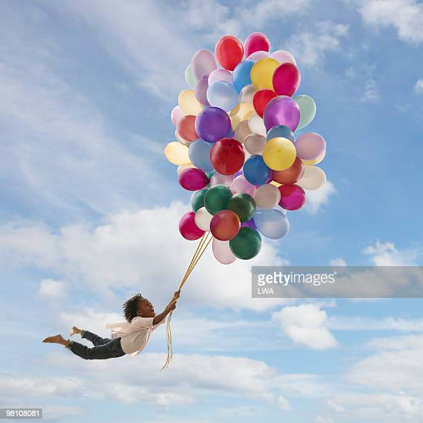 Girl Holding Onto Balloons, Floating In The Air