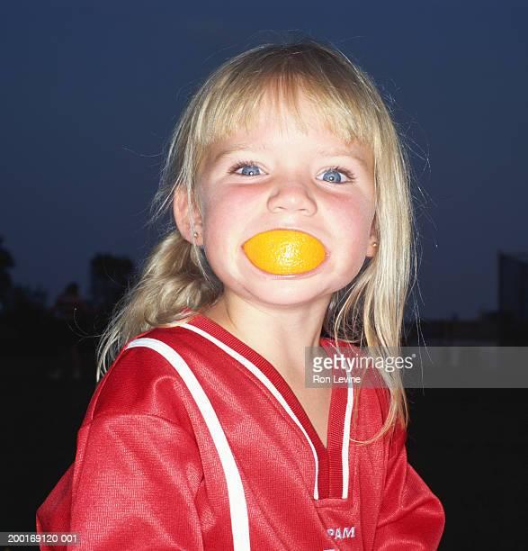 Girl (4-6) holding orange in mouth, portrait
