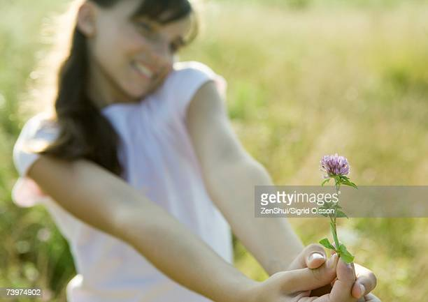 girl holding out flower, focus on flower in foreground - little girls giving head stock photos and pictures