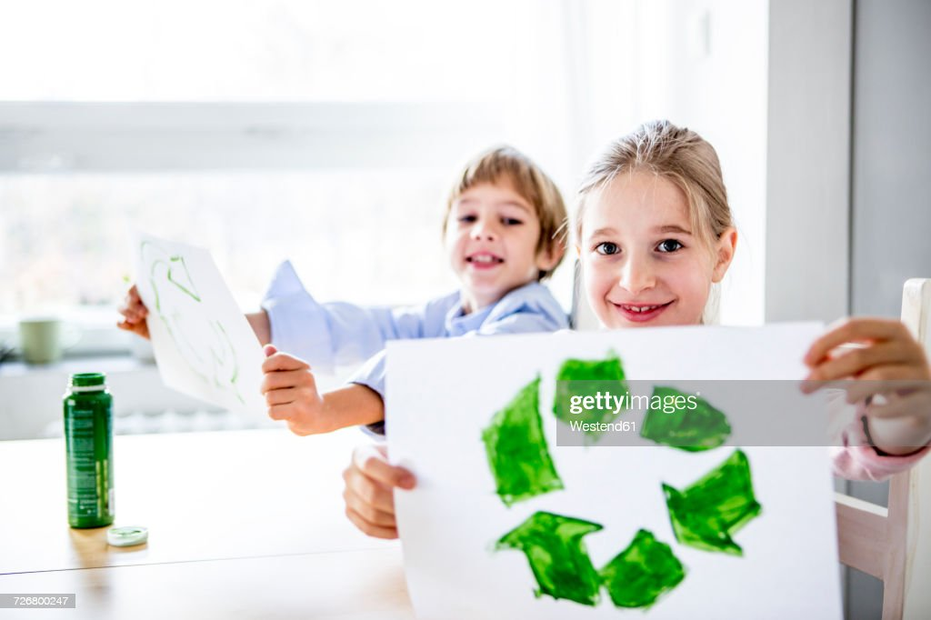 Girl holding paper with painted recycling symbol : Stock Photo