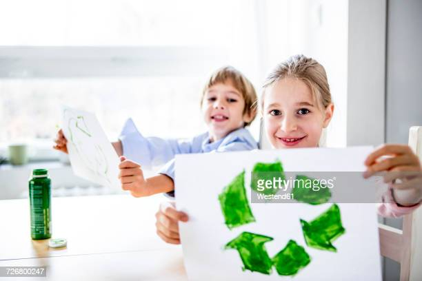 Girl holding paper with painted recycling symbol