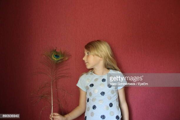 Girl Holding Peacock Feather Against Wall
