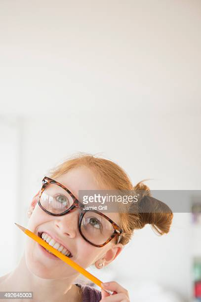 Girl (12-13) holding pencil in mouth, Jersey City, New Jersey, USA
