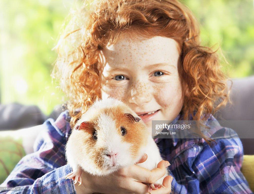 Girl holding pet hamster in living room : Stock Photo