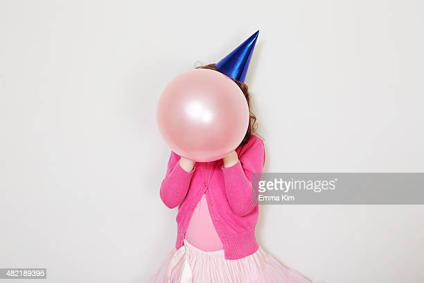 Girl holding pink balloon in front of face