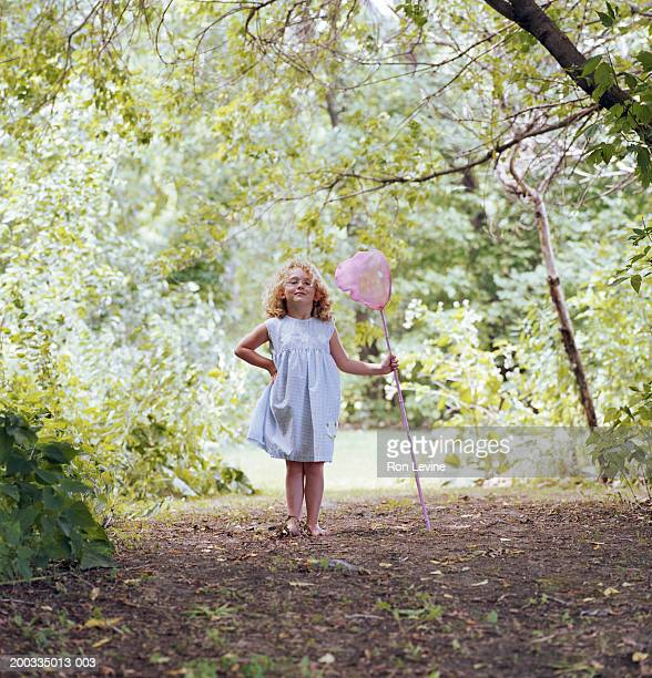 Girl (5-7) holding pink butterfly net in wooded area, portrait