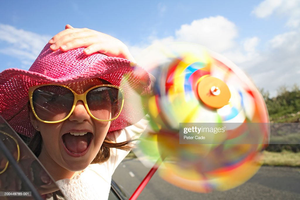 Girl (9-11) holding pinwheel, sticking head out car (blurred motion) : ストックフォト