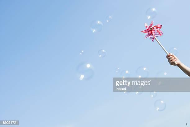 Girl holding pinwheel to the sky