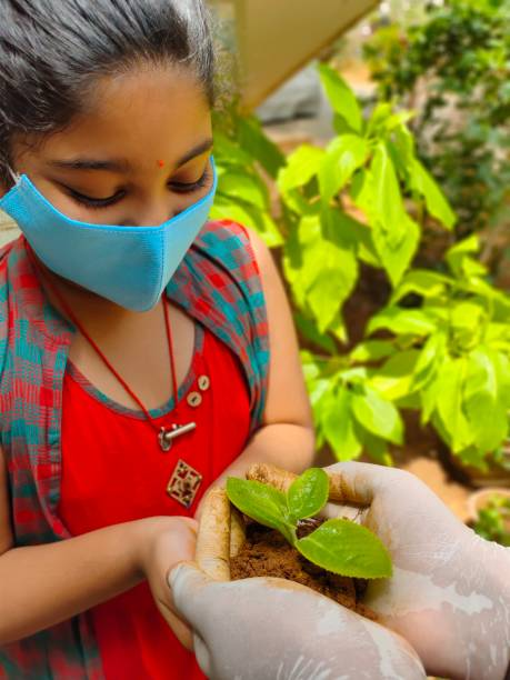 Girl Holding Plant Outdoors
