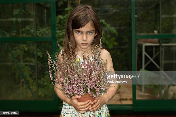 Girl holding plant outside greenhouse