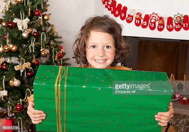 Girl holding present at Christmas tree