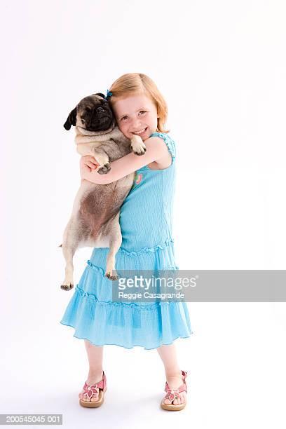 Girl (5-6) holding pug, portrait