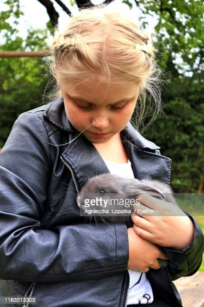 Girl Holding Rabbit While Standing Outdoors