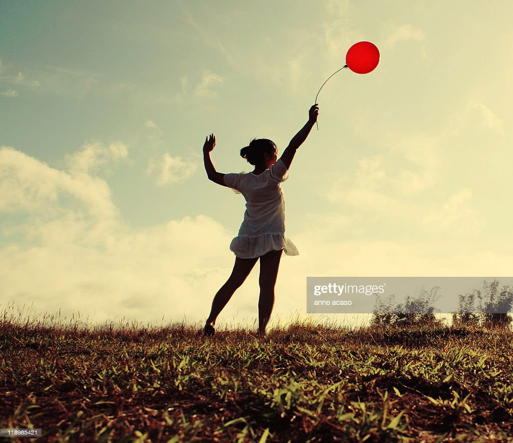 Girl holding red balloon : Stock Photo