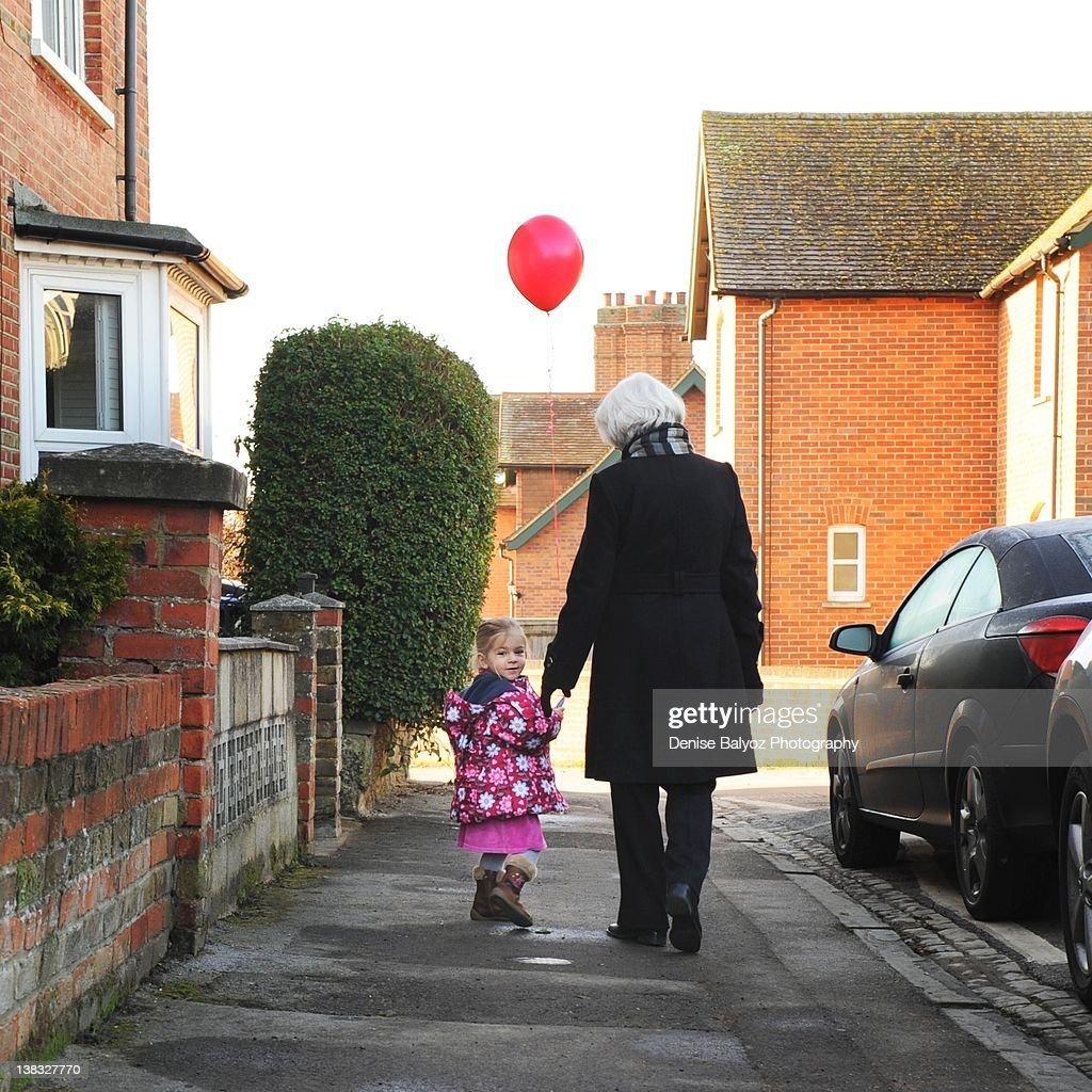 Girl holding red balloon with grandmother : Stock Photo