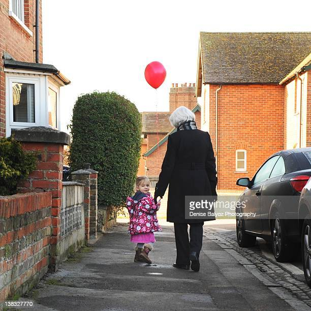 Girl holding red balloon with grandmother