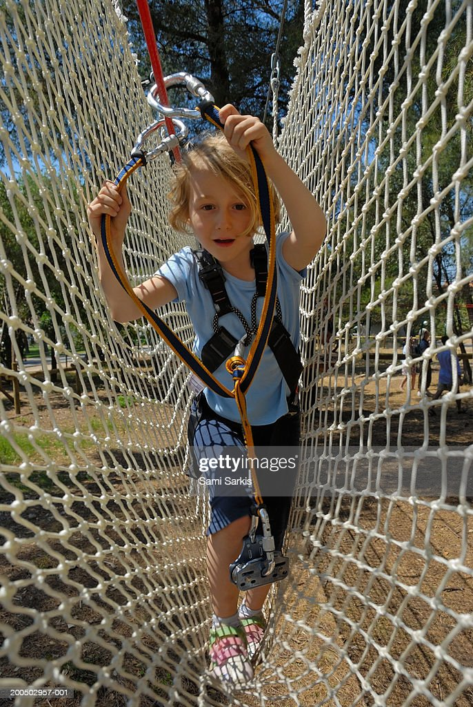 Girl (5-7), holding rope, crossing netting in adventure playground : Stock Photo