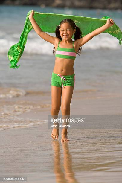 girl (5-7) holding sarong on beach, arms raised, smiling - chinese bikini girls stock pictures, royalty-free photos & images