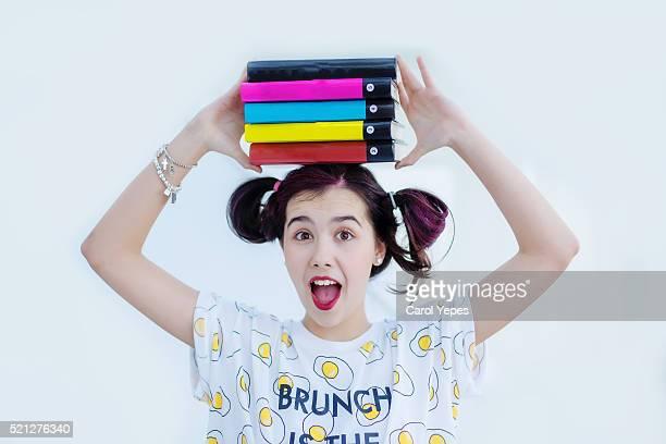 girl holding school books over her head