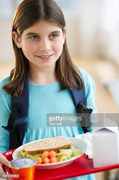Girl holding school lunch tray