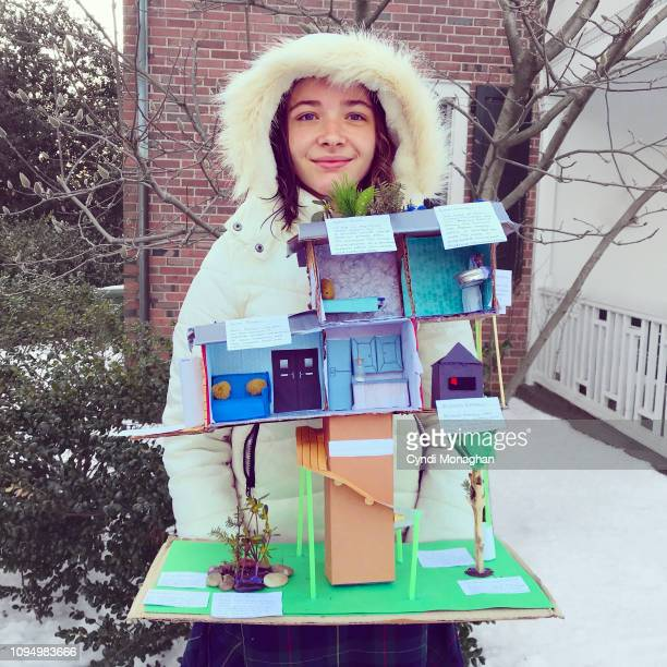 Girl Holding School Project of Energy Efficient and Sustainable House Model
