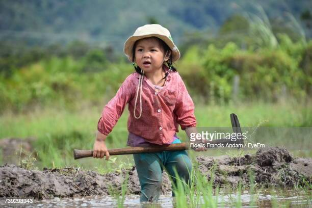 girl holding shovel while standing at rice paddy - francis spade photos et images de collection