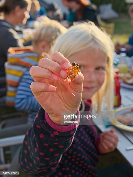 Girl holding shrimps at a barbecue on a camping ground