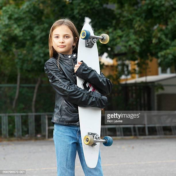 Girl (8-10) holding skateboard, portrait