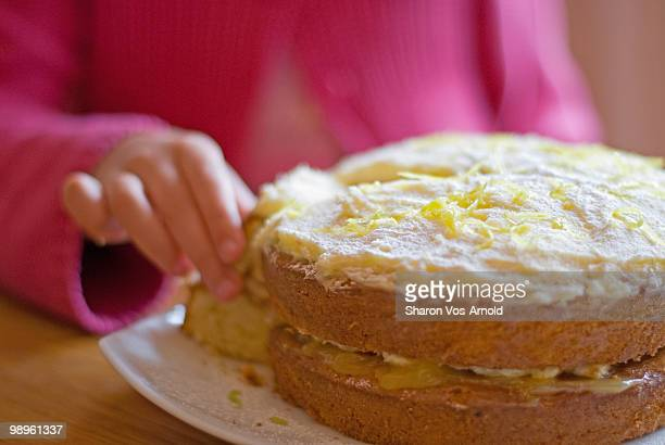 Girl holding slice of home baked lemon sponge cake