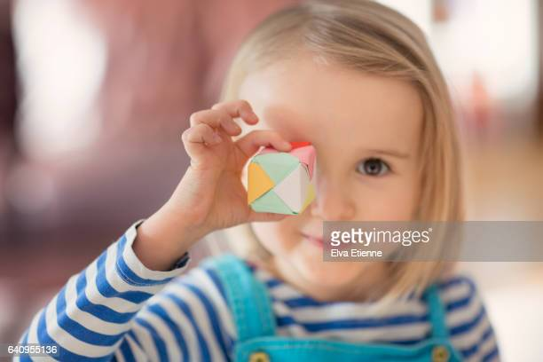 Girl holding small paper origami cube