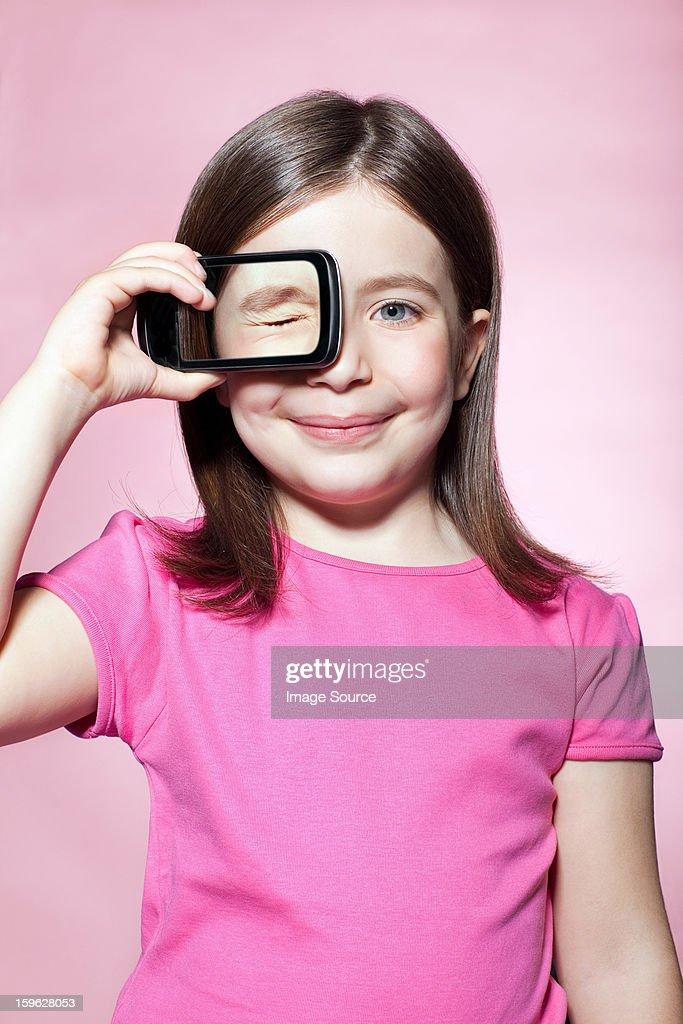 Girl holding smartphone over eye : Stock Photo