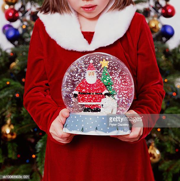 Girl (6-7 years) holding snow globe in front of christmas tree, mid section