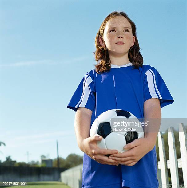 girl (8-10) holding soccer ball, low angle view - football strip stock pictures, royalty-free photos & images