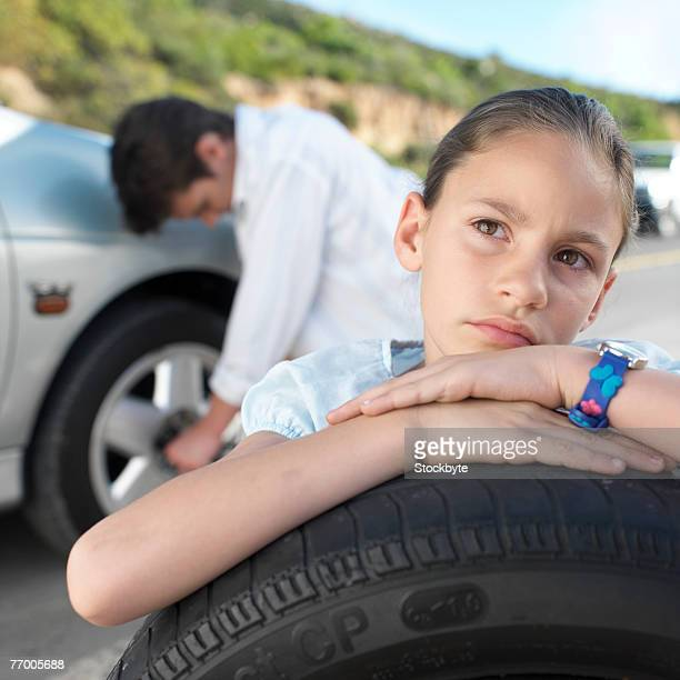 girl (8-9 years) holding spare tire, father changing flat tire in background - 25 29 years stock pictures, royalty-free photos & images