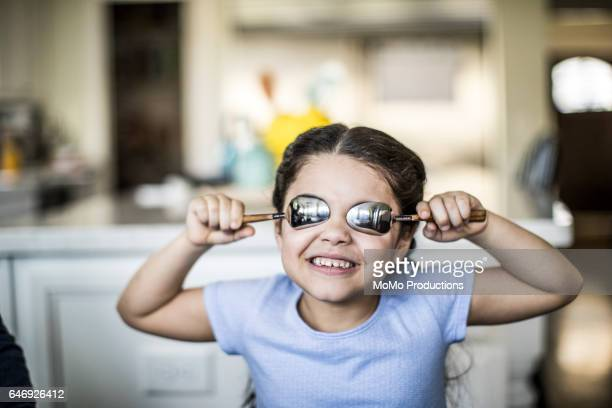 girl (7yrs) holding spoons over eyes - naughty america stock pictures, royalty-free photos & images