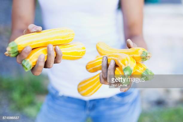 Girl holding squash at an organic farm, close-up