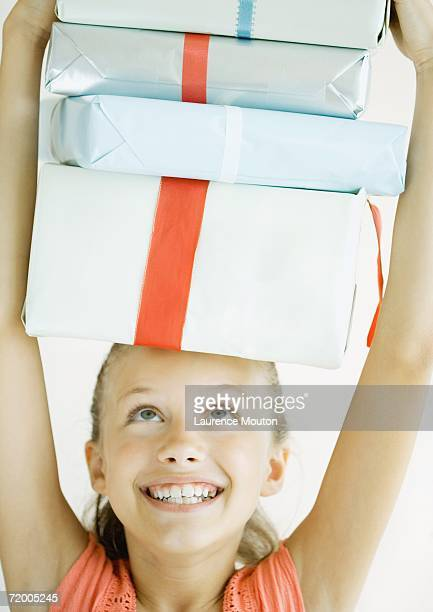 girl holding stack of presents on head - little girls giving head stock photos and pictures